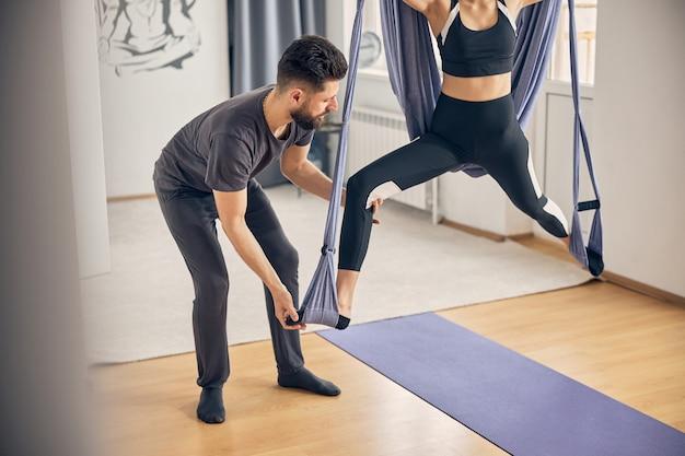 インストラクターが彼女の足を正しい位置に保持している間、ハンモックで運動をしている女性にクローズアップ