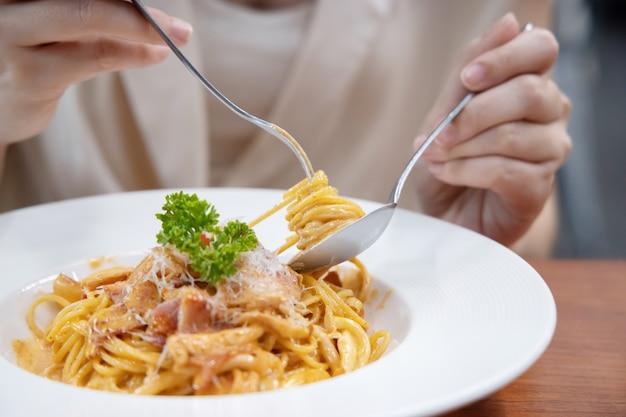 フォークでカボナーラスパゲッティを食べる女性のクローズアップ