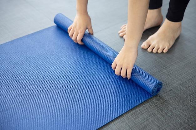 ヨハクラスの後に地面に青いヨガマットを折りたたむ女性のクローズアップ