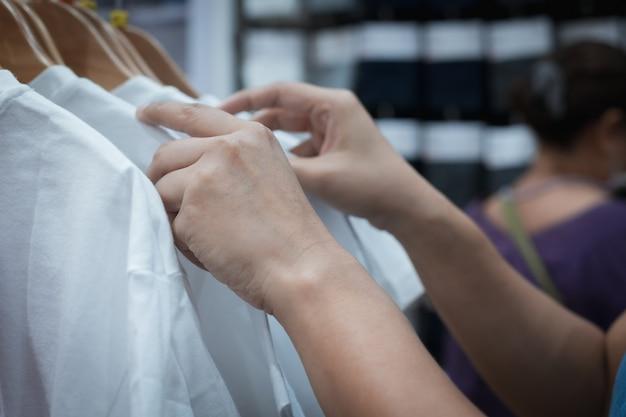 Крупным планом на руке женщины, выбирая одежду футболки со скидкой в торговом центре
