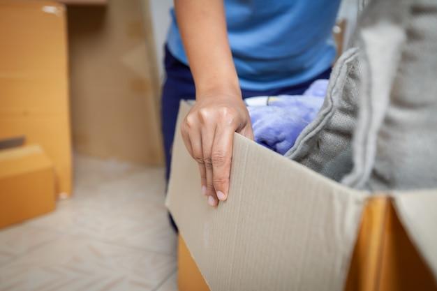 Закройте вверх на руке женщины держа и неся картонную коробку с вещами, перемещающимися в новый дом в день переезда. концепция ремонта и переселения дома.
