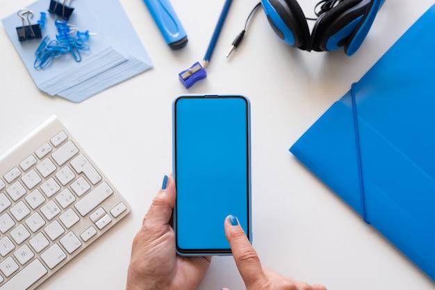Крупный план на руках женщины, держащей смартфон с синим дисплеем. синий цвет на аксессуарах
