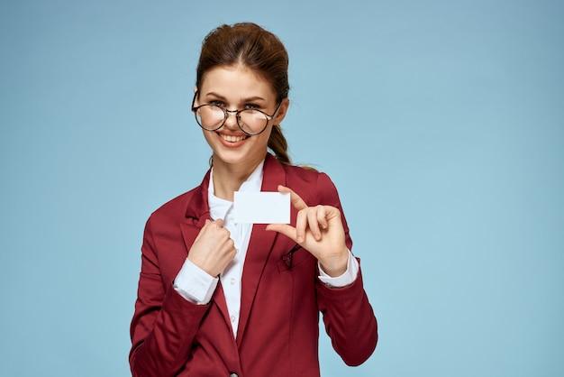Крупным планом женщина в деловом костюме в очках с пустой визитной карточкой