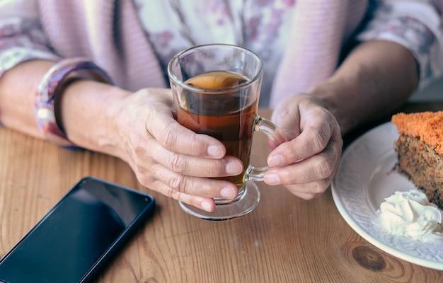 お茶とキャロットケーキを楽しんで、コーヒーショップで女性の手のクローズアップ