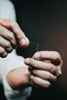 針と糸を縫う女性の手のクローズアップ。無駄な手を働いている老婆。仕立て屋はいくつかの生地を縫います。詳細、低照度、不機嫌