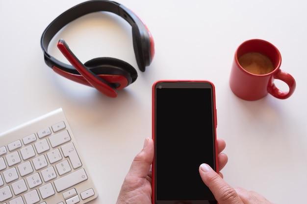 Закройте на руках женщины с помощью мобильного телефона. белый рабочий стол и красные аксессуары