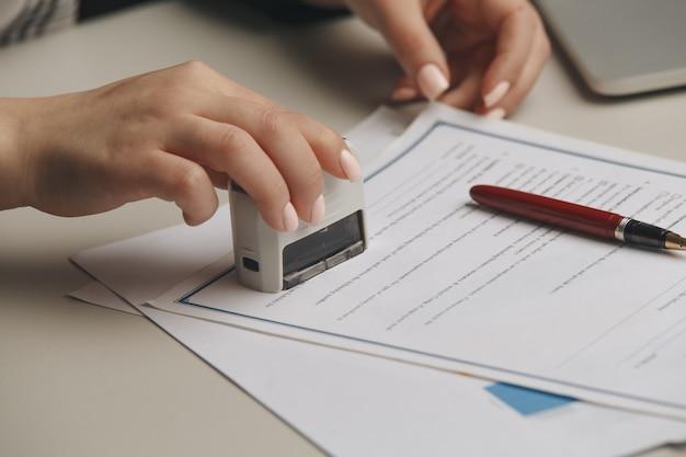 문서를 스탬프하는 여성의 공증인 손에 닫습니다. 공증인 개념.