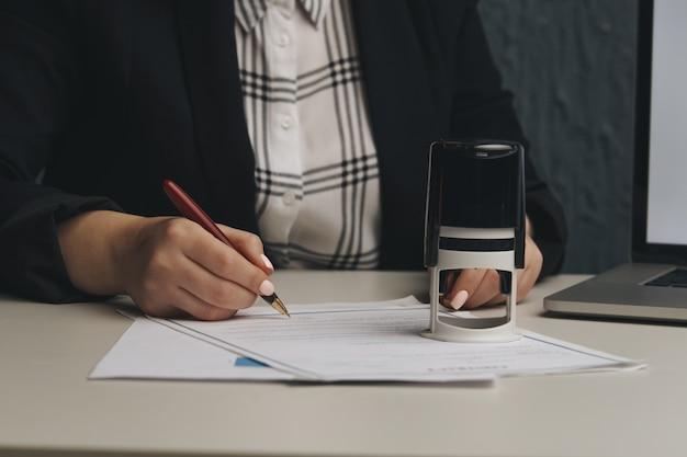 Крупным планом на руку нотариуса женщины печать документа.