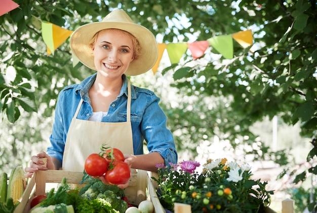 彼女の庭から作物を見ている女性にクローズアップ