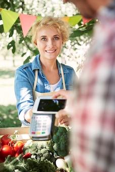 彼女の庭から作物を売っている女性にクローズアップ