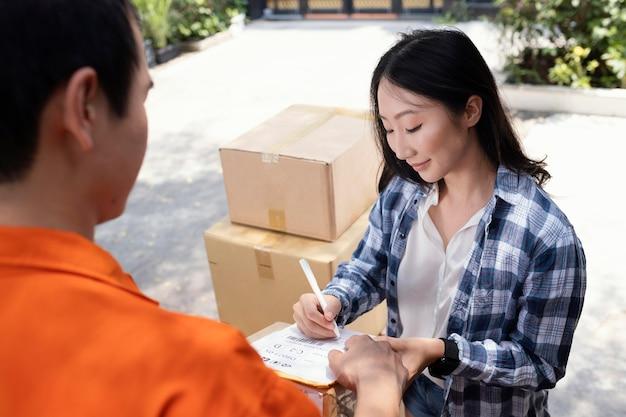 小包の配達のために署名する女性にクローズアップ