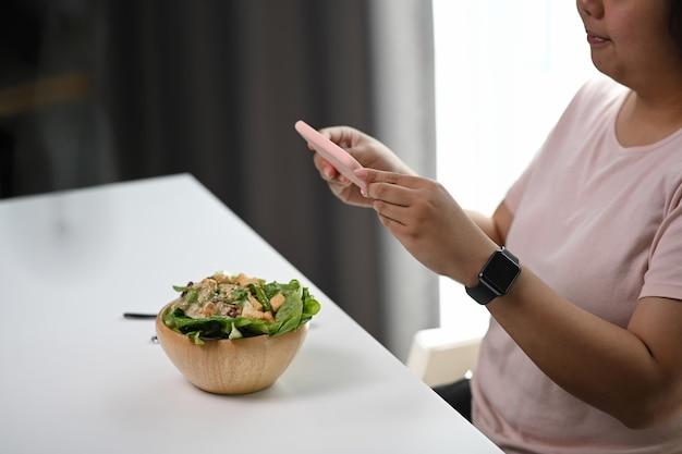 Крупным планом женщина с помощью смартфона фотографирует салат