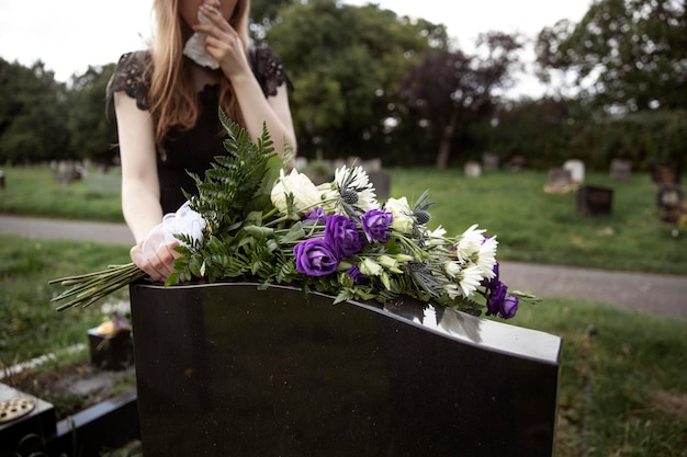 사랑하는 사람의 무덤을 방문하는 여자를 닫습니다