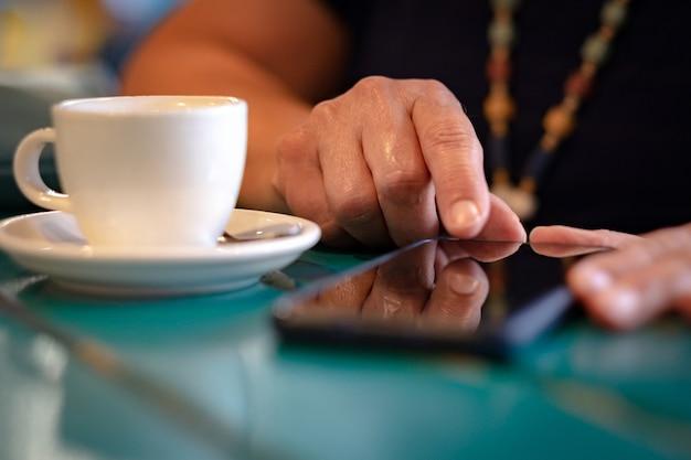 테이블에 흰색 커피 컵을 들고 휴대폰으로 메시지를 보내는 여성을 가까이서 보세요. 앉아서 기술과 사교를 즐기는