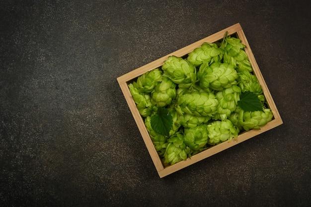 Крупным планом на деревянной коробке свежего зеленого хмеля на столе