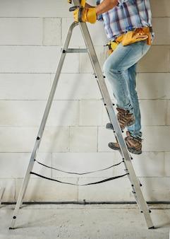 はしごの上に立っている労働者にクローズアップ