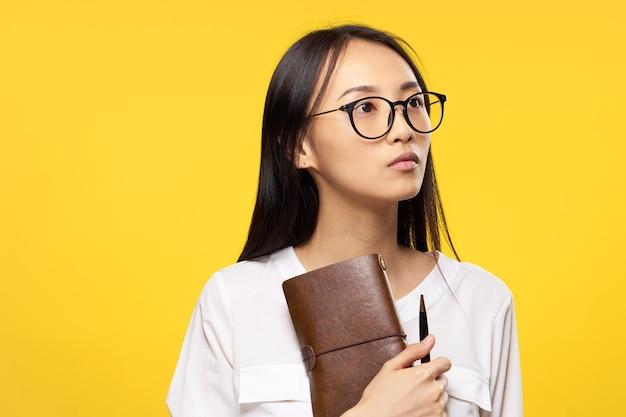 ノートを保持している若いアジア女性にクローズアップ