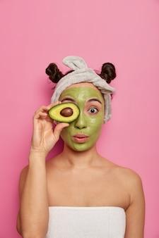 顔のマスクを持つ若い美しい女性にクローズアップ