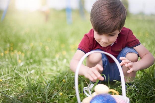 カラフルなイースターエッグを見ている少年にクローズアップ