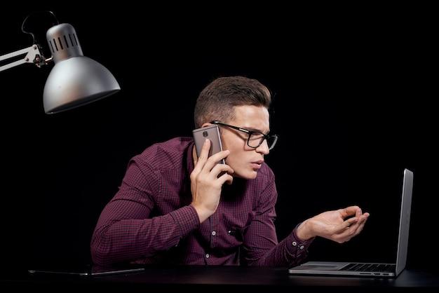 彼の机に座っている青年実業家にクローズアップ