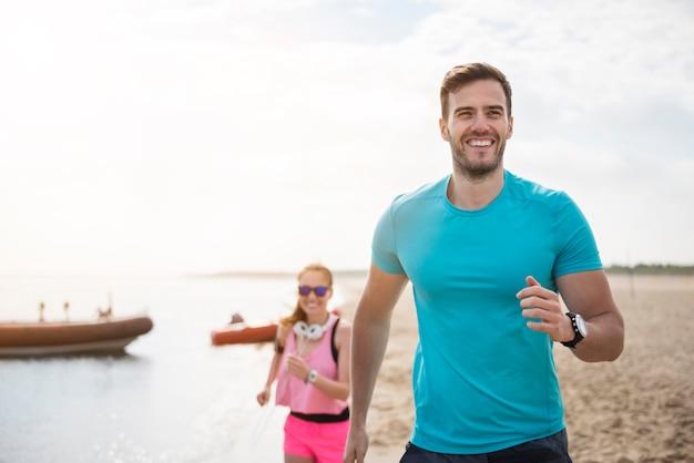 海でジョギングしている若い健康な人々にクローズアップ