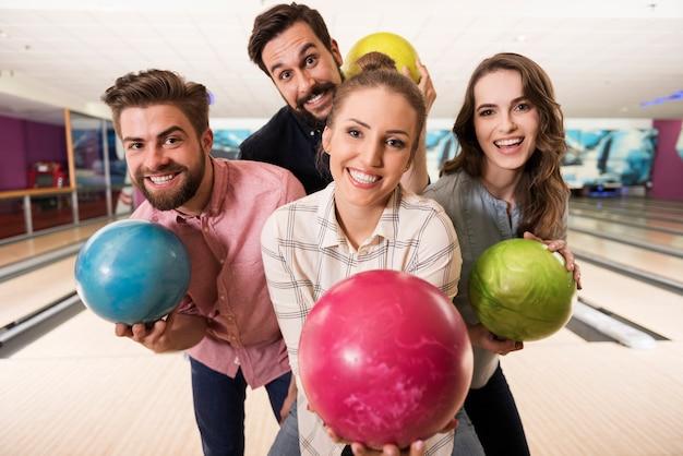 Крупным планом молодых друзей, наслаждающихся боулингом