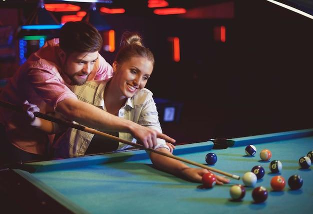 Крупным планом молодые друзья веселятся во время игры в бильярд