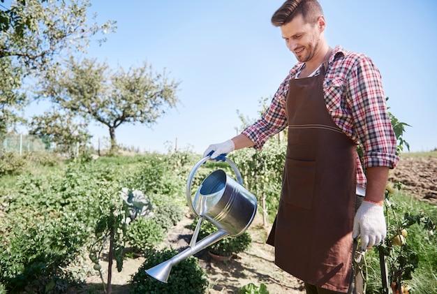 彼の庭の世話をしている若い庭師にクローズアップ