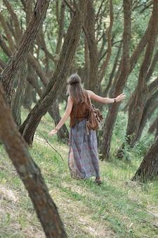 숲에있는 나무 사이에 서있는 젊은 히피 여자에 가까이