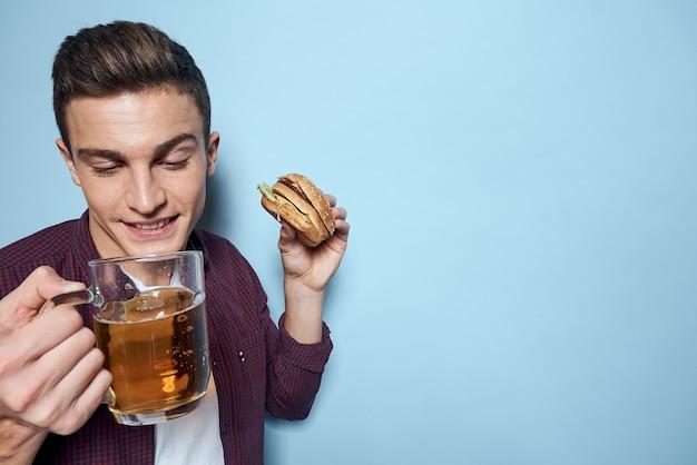 Крупным планом молодой человек ест нездоровую пищу и пьет пиво