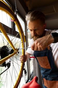 自転車に取り組んでいる若い男にクローズアップ