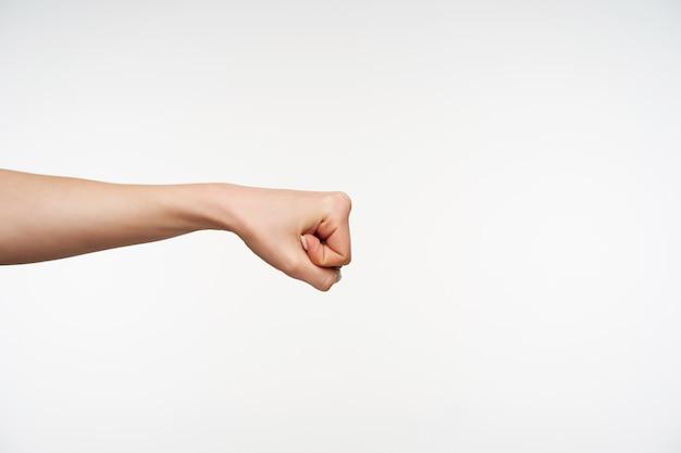 拳に指を食いしばっている間上げられている若いきれいな女性の手をクローズアップ