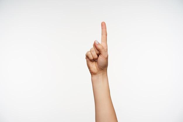 Крупным планом рука молодой красивой дамы поднимает указательный палец вверх, указывая вверх