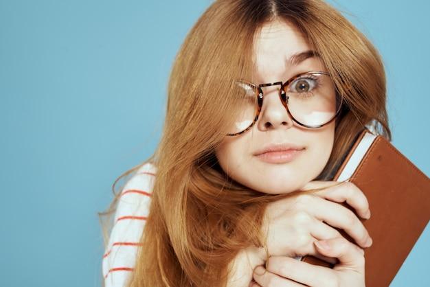 Крупным планом на молодого студента с учебниками и очками