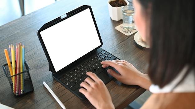 디지털 태블릿의 키보드에 입력하는 젊은 여성 디자이너에 닫습니다