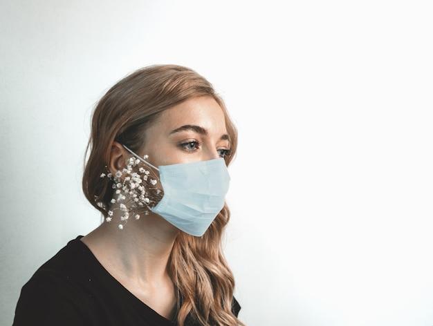 花と医療マスクで若い女性にクローズアップ