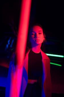 劇的な光の中でポーズをとる若い女性にクローズアップ