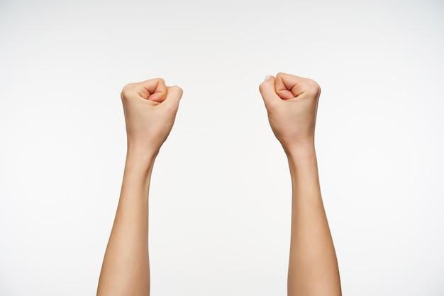 손가락을 주먹으로 움켜 쥐는 동안 젊은 여자의 손이 제기되는 것을 닫습니다.