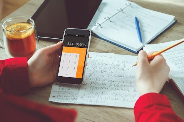 Крупным планом молодая женщина решает математические формулы