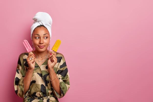 頭にローブと包まれたタオルを身に着けている若い女性にクローズアップ