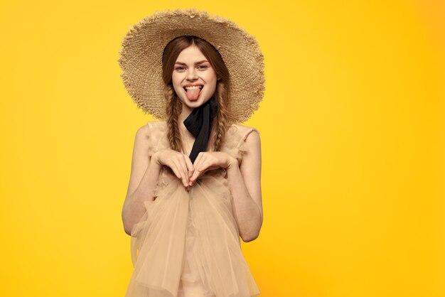 麦わら帽子を持つ若い女性をクローズアップ
