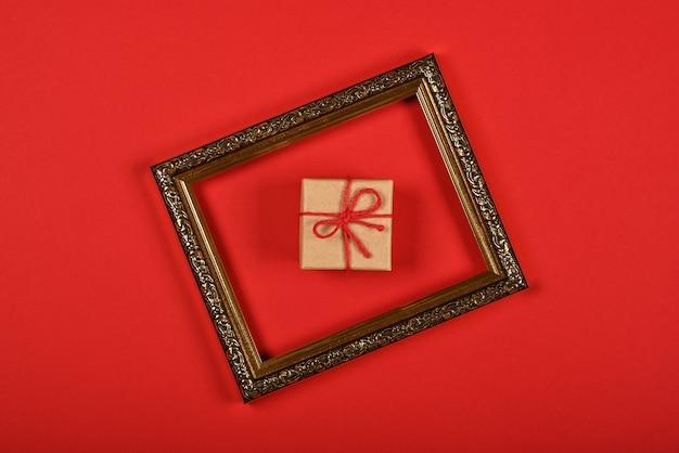 바로 위에 빨간색 배경, 평평한 위치, 높은 평면도 위에 골든 프레임에 갈색 종이 선물 상자 하나를 닫습니다.