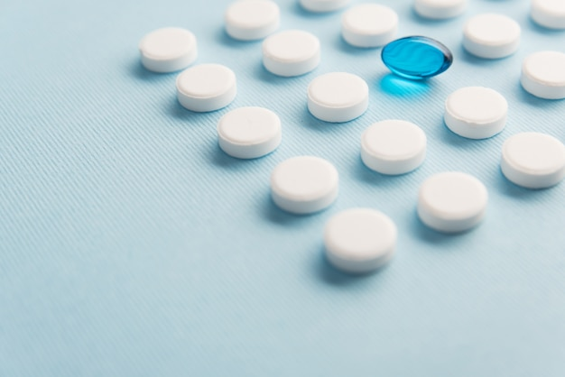 Close up of one capsule surrounded by white tablets