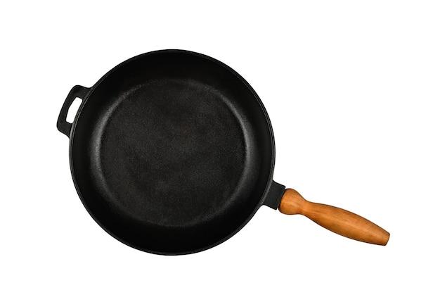 Закройте одну пустую черную чугунную сковороду с деревянной ручкой, изолированной на белом фоне, прямо над