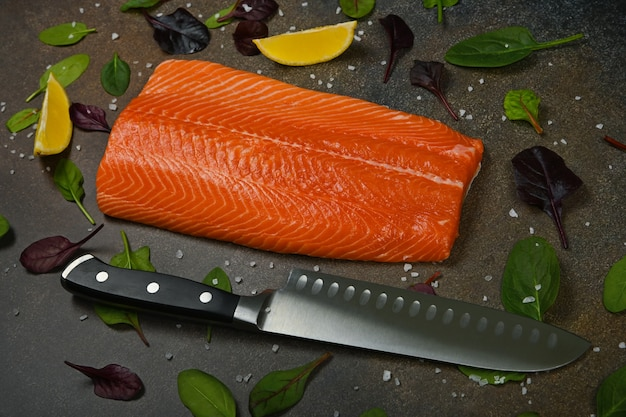Close up one fresh raw salmon fish fillet on table, with kitchen knife, lemon wedges, and salad leaves, high angle view