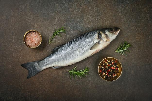 塩、コショウの実、ローズマリー、高架の上面図、真上にある、テーブルの上にある新鮮な生のシーバスの魚をクローズアップします。