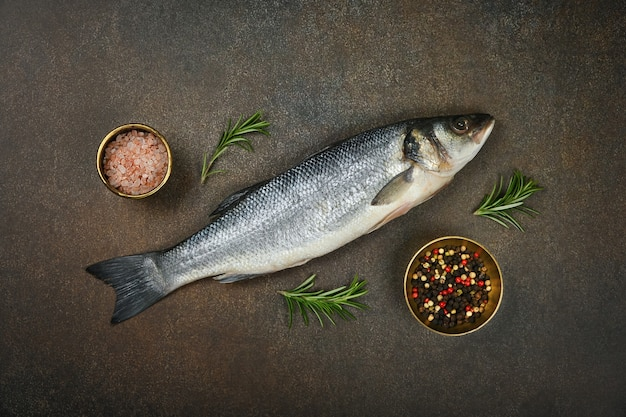 Close up one fresh raw sea bass fish on table, with salt, peppercorns and rosemary, elevated top view, directly above