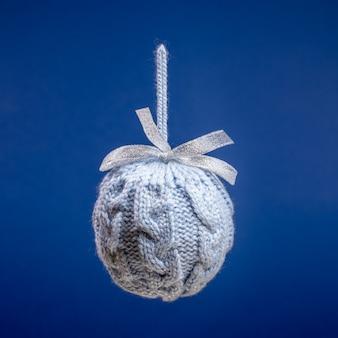 Закройте один висит серый вязаный творческий рождественский шар на ярко-синем квадрате