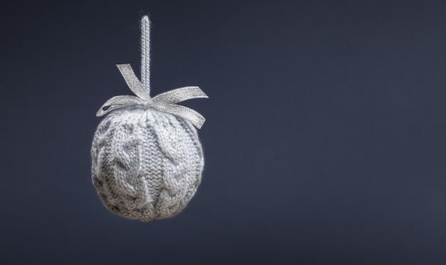 Крупным планом один висит серый вязаный творческий рождественский шар на сером