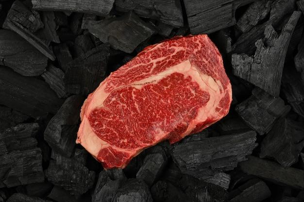 바비큐 그릴 요리를 위해 준비된 검은 덩어리 숯 조각에 대리석으로 된 원시 ribeye 쇠고기 스테이크 하나를 닫습니다.